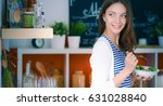 young woman eating salad and... | Shutterstock . vector #631028840