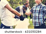little boys picking up plastic... | Shutterstock . vector #631050284