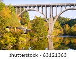 A scenic excursion train passes under a high arch bridge - stock photo
