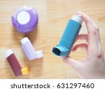 Small photo of Patient's hands holding blue asthma inhaler with set of asthma/COPD inhalers on wood table. Pharmaceutical products for treat lung inflammation and relief asthma attack. Health and medical concept.