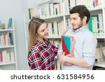 Stock photo beautiful young confident girl flirting with shy geeky guy at the library young male student 631584956