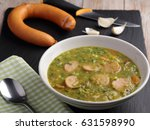 Small photo of Dutch pea soup snert with smoked sausage Rookworst on a rustic table