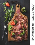 Small photo of Turkish pastirma with strawberry and arugula. Highly seasoned, air-dried cured beef meat cut in slices on wooden board over dark background, top view