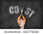 Small photo of Businessman holding a scissor cutting cost text on blackboard background.