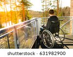 Small photo of Young lonely man in a wheelchair on a balcony looking at the nature in the spring