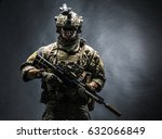 Army soldier in Combat Uniforms with assault rifle, plate carrier and combat helmet are on, Shemagh Kufiya scarf on his neck. Studio shot, dark background - stock photo