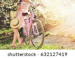 Stock photo vintage bike concept beautiful and young girl in pink dress standing with retro bike on green 632127419