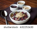 Small photo of A bowl of oatmeal with dried fruit, brown sugar and diced almonds displayed with the accouterments and spoon