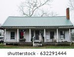 Small photo of Texan Hospitality - Texan farmhouse, complete with Flag of Texas and porch chairs.