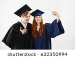 Small photo of Two graduate friends in caps and mantles laughing making selfie over white background before receiving their magister diploma or bachelor of arts or other academic degree. Study concept.