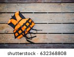 orange life vest on wooden... | Shutterstock . vector #632368808