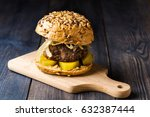 Small photo of Beef burger on a plate with braised onion and marinated cucumbers
