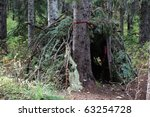Primitive survival shelter in a forest - stock photo