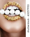 Woman open mouth with gold leaf make-up and teeth biting on faux pearls. - stock photo