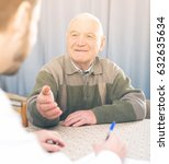 Small photo of Senior man preparing agreement papers with social worker at home