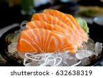 Raw salmon slice or salmon sashimi in Japanese style fresh serve on ice with fresh wasabi photo in  indoor low lighting.