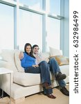 smiling couple sitting on sofa | Shutterstock . vector #632986499
