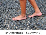 Walking Bare-Footed On Textured Stone Surface - stock photo