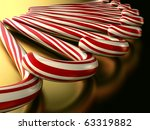 A render of a pile of candy canes over a gold surface - stock photo
