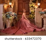 Stock photo beautiful woman in a luxurious pink dress background of a beautiful yard decorated with flowers 633472370