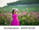 Stock photo a beautiful romantic woman in a pink dress and hat strolls through the flowering gardens of a tea 633476120