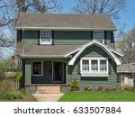 Small photo of Older Two Story Home with Spring Flowers