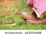 Small photo of Little boy read a book under the big tree, selective soft focus.
