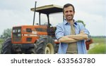 Small photo of Portrait of a handsome young farmer standing in a shirt and smiling at the camera, on a tractor and nature background. Concept: bio ecology, clean environment, beautiful and healthy people, farmers.