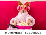 Stock photo chihuahua dog watching tv or a movie sitting on a red sofa or couch with remote control changing 633648026