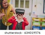 teacher is helping one of her... | Shutterstock . vector #634019576