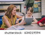 teacher is helping one of her... | Shutterstock . vector #634019594