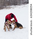 Small photo of Man in red winter jacket holding an Airedale Terrier next to a second identical dog