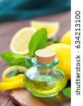 Small photo of Essential aroma oil with mint and lemon on wooden background