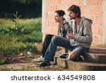 two friends sitting on stairs... | Shutterstock . vector #634549808