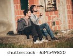 two friends sitting on stairs... | Shutterstock . vector #634549820