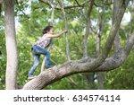 happy little girl climbing a... | Shutterstock . vector #634574114