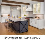 Stock photo kitchen in new luxury home with large island hardwood floors range hood and glass fronted 634668479