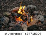 Small photo of Evening small fire made of birch logs ennobled with stones. Warm hearth.