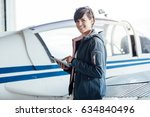 smiling female pilot connecting ... | Shutterstock . vector #634840496