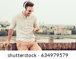 young man listening to music on ... | Shutterstock . vector #634979579
