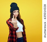 Small photo of Hipster girl in jeans, checked shirt and hat showing middle fingers over yellow background. Impertinent behaviour. Hipsters. Provocation. Aggression. Naughtiness.