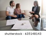 Small photo of Young renters couple sitting on couch discussing renting apartment with real estate agent, focus on rental agreement and keys, property lease contract. Looking for accommodation, long-term tenancy