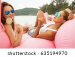 Small photo of Summer lifestyle portrait of two pretty girls friends on the beach with yummy lollipops, wearing white t-shirts, short denim shorts and mirrored sunglasses. Smiling and having fun. Positive emotions