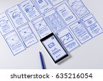 Small photo of Paper sketches for mobile interface design. Designing responsive content for mobile website