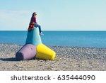 Small photo of Woman sitting on a concrete tetrapod on the beach