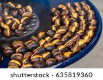 fried chestnuts on the street.... | Shutterstock . vector #635819360