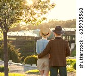 Small photo of A couple in love at sunset in hats stand with their backs in the frame. American dream. A retro couple in his country house, his estate. Lavstory, family day, St. Valentine's Day.