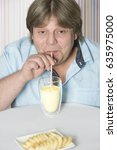 Small photo of Like able man drinks milk Shake banana with straw