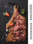 Small photo of Turkish pastirma with strawberry. Highly seasoned, air-dried cured beef meat cut in slices on wooden board over dark background, top view