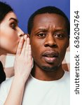 Small photo of Gossip white woman whispering on ear to black man, closeup. Girl unable to keep important secret. Tattle and hearsay concept